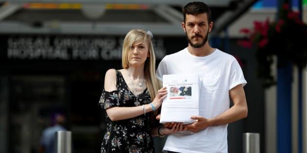 Los padres de Charlie, Connie Yates y Chris Gard, posan con su petición para el tratamiento del bebé en el hospital donde está ingresado el niño, en Londres.