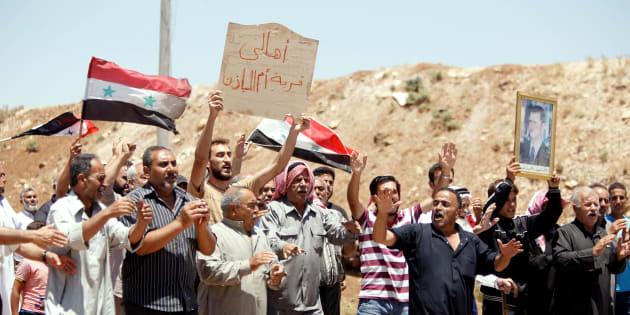 Un grupo de civiles celebra la entrada de las tropas del régimen en Deraa.