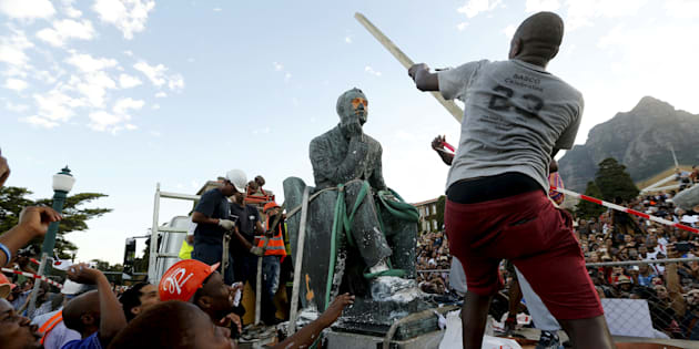 A student hits the statue of Cecil John Rhodes with a stick as it is removed from the University of Cape Town (UCT), April 9, 2015.
