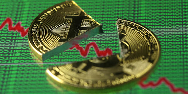 Broken representation of the Bitcoin virtual currency, placed on a monitor that displays stock graph and binary codes, are seen in this illustration picture, Dec. 21, 2017.