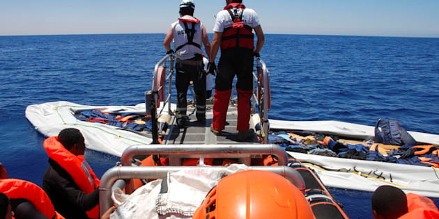 Nick Romaniuk (L) and Max Avis of the NGO SOS Mediterranee take a last look at a rubber boat that they destroyed so that it cannot be used again by people smugglers off the coast of Western Libya May 18, 2017. Picture taken May 18, 2017. REUTERS/Steve Scherer