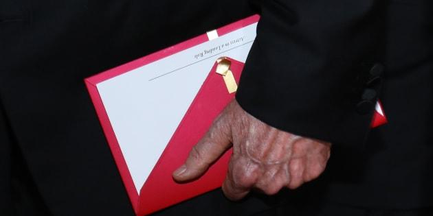 O apresentador Warren Beatty segura o evelope contendo o Oscar de 'Melhor Ator'