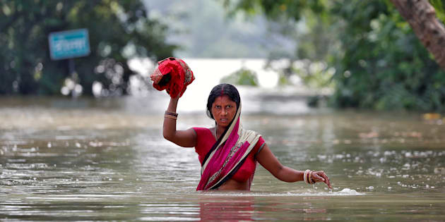 A woman wades through a flooded village in the eastern state of Bihar, India August 22, 2017. REUTERS/Cathal McNaughton     TPX IMAGES OF THE DAY