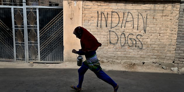 A girl runs with a milk pot through a deserted street in Srinagar as the city remains under curfew following weeks of violence in Kashmir.