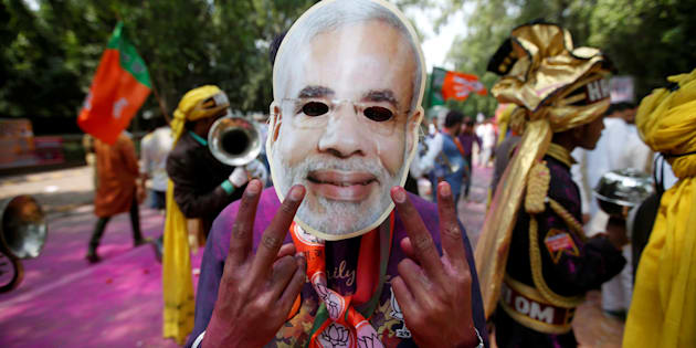 A supporter of India's Bharatiya Janata Party (BJP) celebrates after learning of the initial poll results outside the party headquarters in New Delhi, India, March 11, 2017. REUTERS/Adnan Abidi