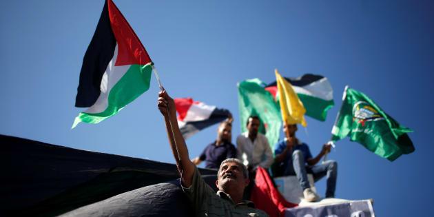 Un grupo de palestinos celebran en Gaza el acuerdo de Hamás y Fatah, con banderas de su estado y de los dos partidos.