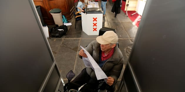 A voter studies a list of candidates for the general election in Amsterdam.