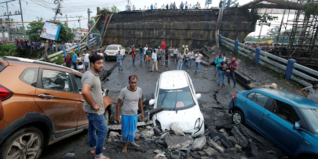 People stand next to the wreckage of vehicles near the Majerhat bridge, which collapsed on Tuesday.