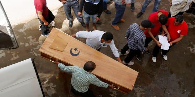 Un grupo de personas traslada el cuerpo de uno de los migrantes ahogados, en la morgue de Sfax, Túnez.