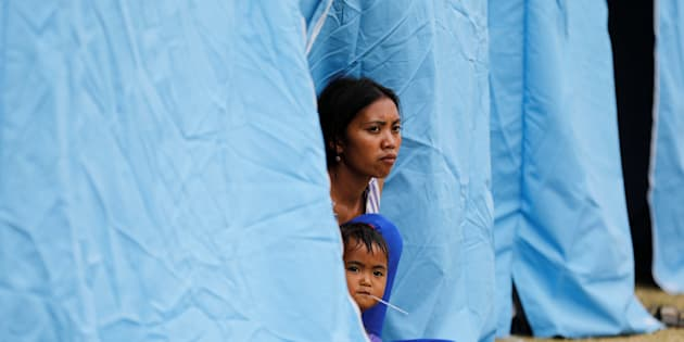 A woman and child sit in a tent at a temporary evacuation center for people living near Mount Agung, a volcano on the highest alert level, outside a sports arena in Klungkung, on the resort island of Bali, Indonesia, September 24, 2017.