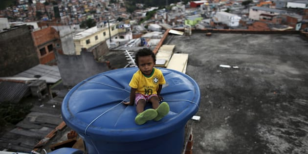 Igor, 6, sits on a water container, on the roof of his house in Brasilandia slum, in Sao Paulo, Brazil, February 10, 2015. Picture taken on February 10, 2015. REUTERS/Nacho Doce