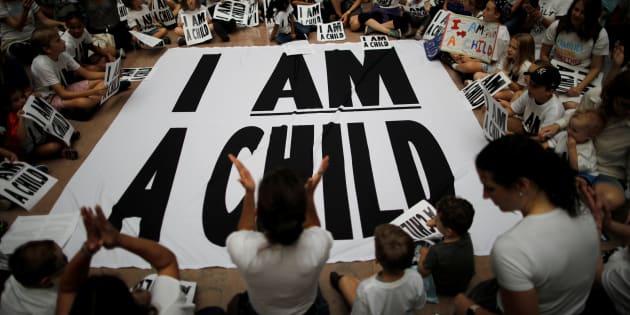 """Los niños y los familiares participan en una sentada después de una marcha para marcar """"el plazo ordenado por la corte para que la administración Trump reúna a miles de familias separadas en la frontera, en Washington, EU."""
