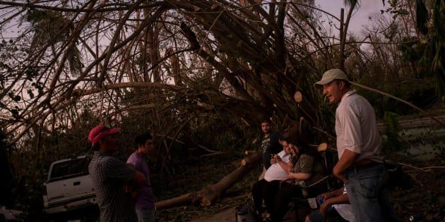 Una familia de inmigrantes mexicanos, ante su casa destrozada en Naples, Florida.