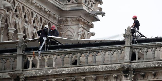 Alpinisti al lavoro per coprire Notre Dame con un telone ant