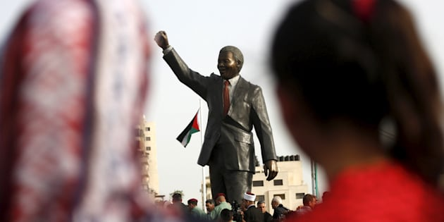 People look at a Mandela statue during the inauguration of Nelson Mandela Square in the West Bank city of Ramallah April 26, 2016.