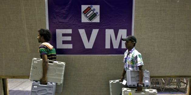 Members of election staff carry electronic voting machines (EVM).