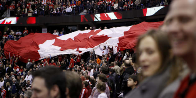 Fans pass around a giant Canadian flag during the singing of the national anthem as the Ottawa Senators prepare to play the Calgary Flames' in Ottawa Feb. 9, 2010.