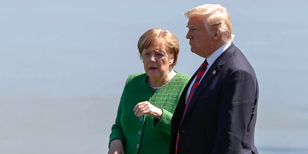 Germany's Chancellor Angela Merkel talks with U.S. President Donald Trump at a family photo session with the leaders of the G7 summit in Charlevoix, Que.
