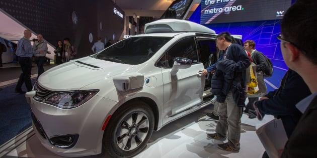 Des curieux regardent la voiture Waymo, anciennement le projet de voiture autonome de Google, lors du CES 2019 de Las Vegas.