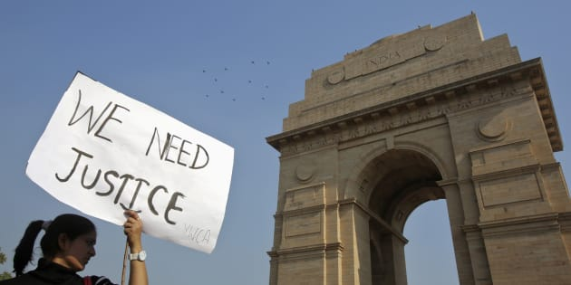 A demonstrator holds a placard in front of the India Gate.