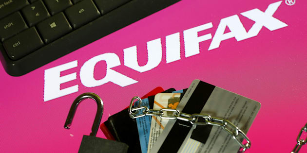 Credit cards, a chain and an open padlock is seen in front of displayed Equifax logo in this illustration taken September 8, 2017.