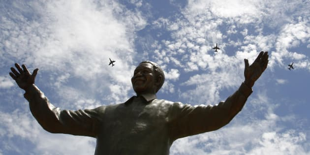 South African military jet fighters fly past a 9-metre (30-feet) bronze statue of the late former South African President Nelson Mandela after it was unveiled as part of the Day of Reconciliation Celebrations at the Union Buildings in Pretoria December 16, 2013.