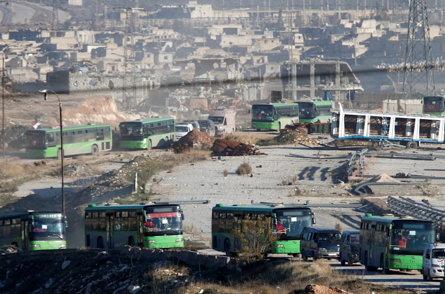 La colonne de bus et d'ambulances qui évacuent Alep-Est au milieu des ruines