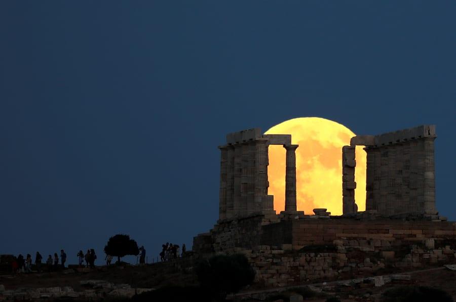 La gente ve una luna llena elevándose detrás del Templo de Poseidón antes de un eclipse lunar en el Cabo Sounion, cerca de Atenas, Grecia.