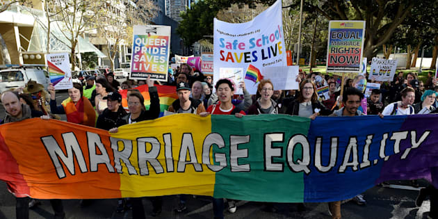 Pro-gay marriage supporters carry a rainbow banner and flags during a rally in Sydney on June 25, 2016.