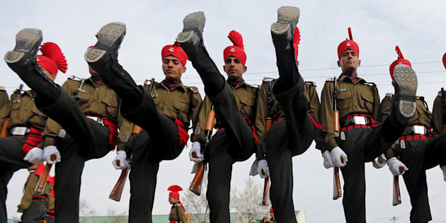 Indian army recruits wearing their ceremonial uniform perform a salute as they pose before their passing out parade at a garrison in Rangreth.