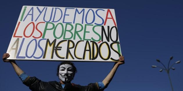 """Un manifestante del movimiento 15-M sujeta una pancarta que dice """"Ayudemos a los pobres no a los mercados"""", en una manifestación en la Puerta del Sol de Madrid con motivo del aniversario en 2014."""