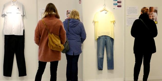 """Un grupo de visitantes repasa las prendas de la exposición """"What Were You Wearing?"""", en Molenbeek (Bruselas)."""
