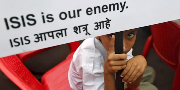 A Muslim boy looks on as he holds a placard at a rally organised by a Muslim charitable trust in Mumbai, India, November 26, 2015. REUTERS/Shailesh Andrade
