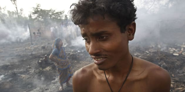 A boy and his mother stand next to their gutted hut after a fire in a slum area in New Delhi April 8, 2010.