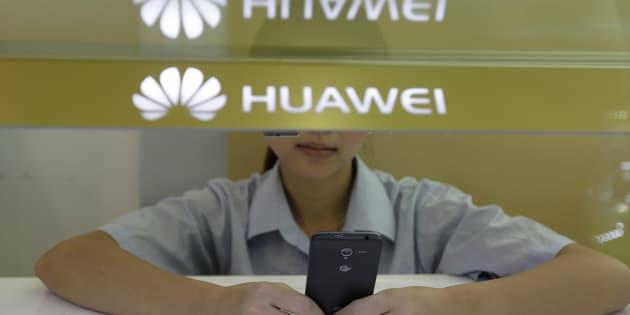 2012年10月10日、中国・湖北省武漢市のファーウェイのカウンターで顧客を待っている女性