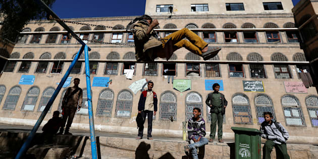 A boy plays on a swing as others watch in a yard of an orphanage in Sanaa, Yemen, in January 2017.