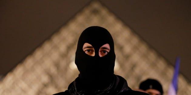 Un policier masqué devant la pyramide du Louvre lors d'une manifestation de policiers le 1er novembre 2016. REUTERS/Christian Hartmann