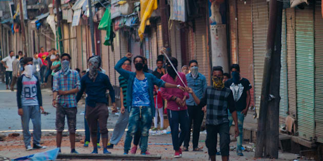 SRINAGAR, KASHMIR, INDIA: Kashmir protesters tries to throw a sling shot at Indian policemen during a curfew in Srinagar.   (Photo by Yawar Nazir/ Getty Images)