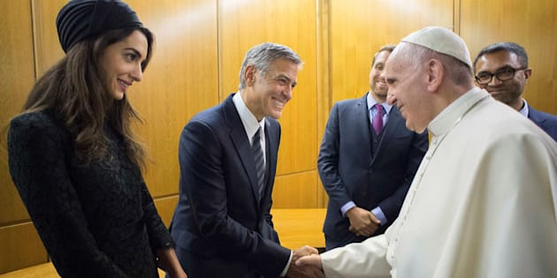George Clooney, with his wife, Amal, shakes the hand of Pope Francis during Sunday's meeting.