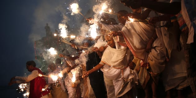 Widows light sparklers after offering prayers as part of Diwali celebrations.