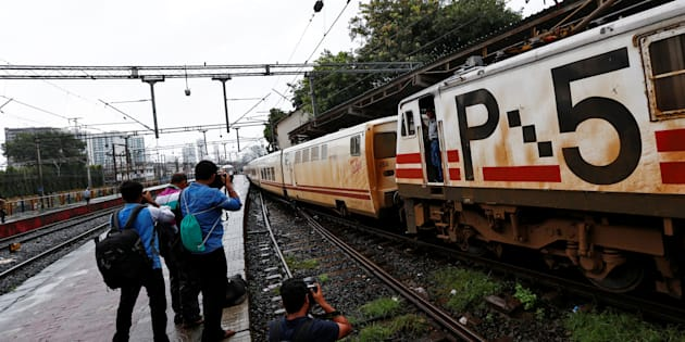 Photographers take pictures of the Talgo train as it arrives at a railway station in Mumbai.
