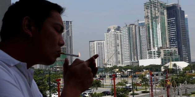 A man lights a cigarette as he takes a break from work at Bonifacio Global City in Taguig, Metro Manila July 4, 2013.   REUTERS/Erik De Castro/File Photo