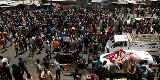 People gather at the scene of a car bomb attack in Baghdad's mainly Shi'ite district of Sadr City, Iraq.