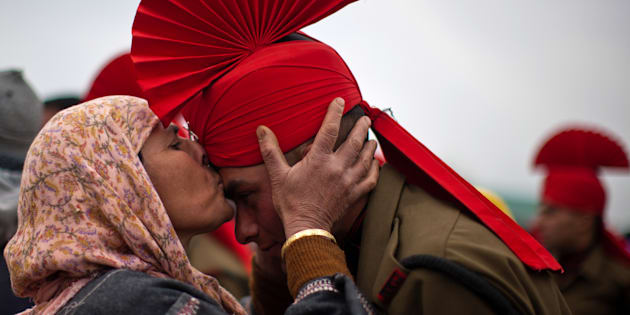 File photo of a Kashmiri Muslim woman kissing  her son after his passing out parade.
