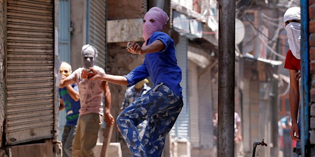 A masked protetser throws pieces of bricks and stones towards Indian police officers during a clash on the occassion of the death anniversary of Burhan Wani, a commander of the Hizbul Mujahideen militant group, in downtown Srinagar July 8, 2017.