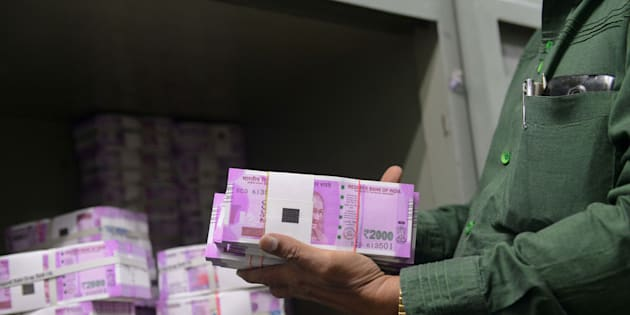 An Indian bank employee checks stacks of new 2000 rupee notes in Ahmedabad.