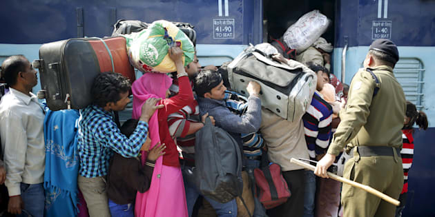 A policeman keeps order as people board a passenger train at a railway station in New Delhi.
