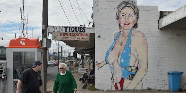 Pedestrians walk past a mural of Democratic presidential nominee Hillary Clinton clad in a skimpy swimsuit.
