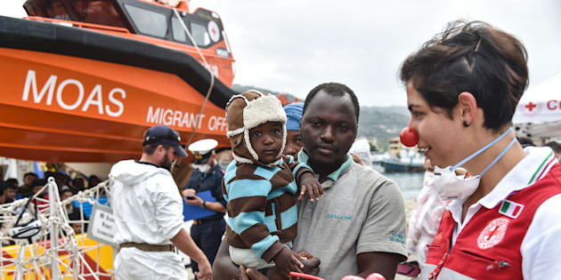 A volunteer of the Italian Red Cross welcomes a man and his baby as they disembark from a rescue ship run by Maltese NGO MOAS, in the habour of Vibo Valentia, southern Italy, on November 7, 2016 / AFP / ANDREAS SOLARO        (Photo credit should read ANDREAS SOLARO/AFP/Getty Images)