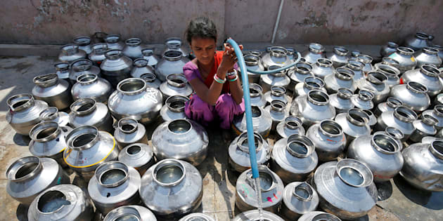 A girl fills metal pitchers with drinking water from a tubewell outside a temple in Ahmedabad, India March 30, 2017. REUTERS/Amit Dave